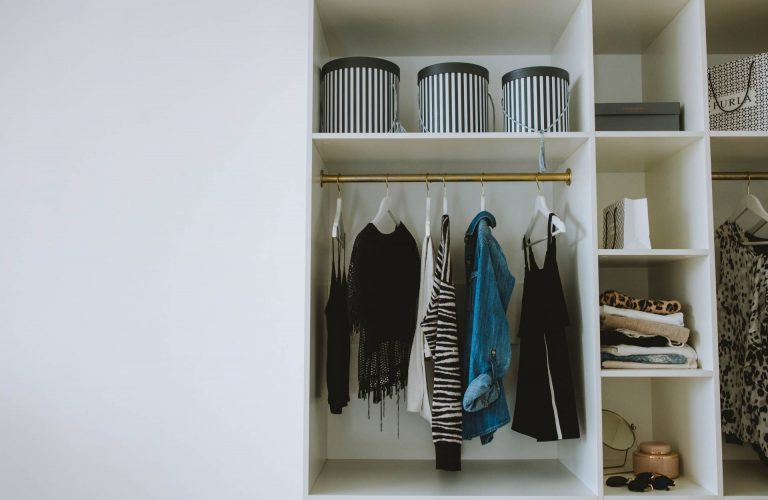 Blue and Black Jackets Hanged on White Wooden Cabinet